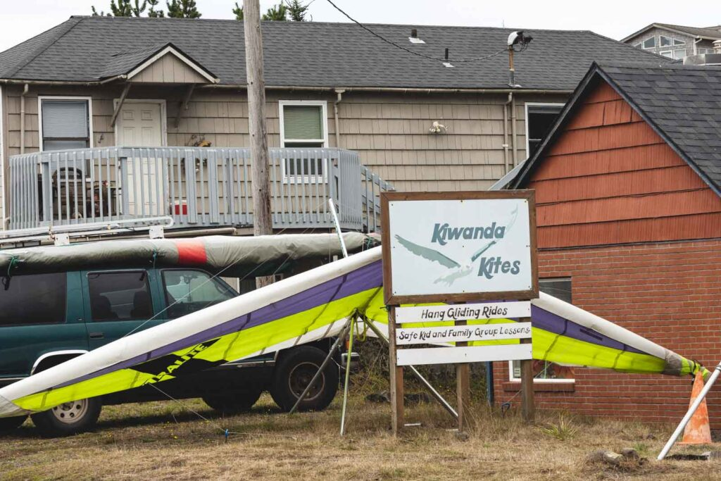 Hang glider stored beside car and in front of building at Pacific City