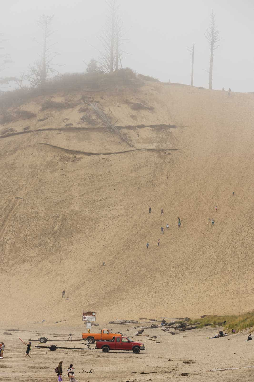 Giant sand dune in the fog with people climbing it at Cape Kiwanda