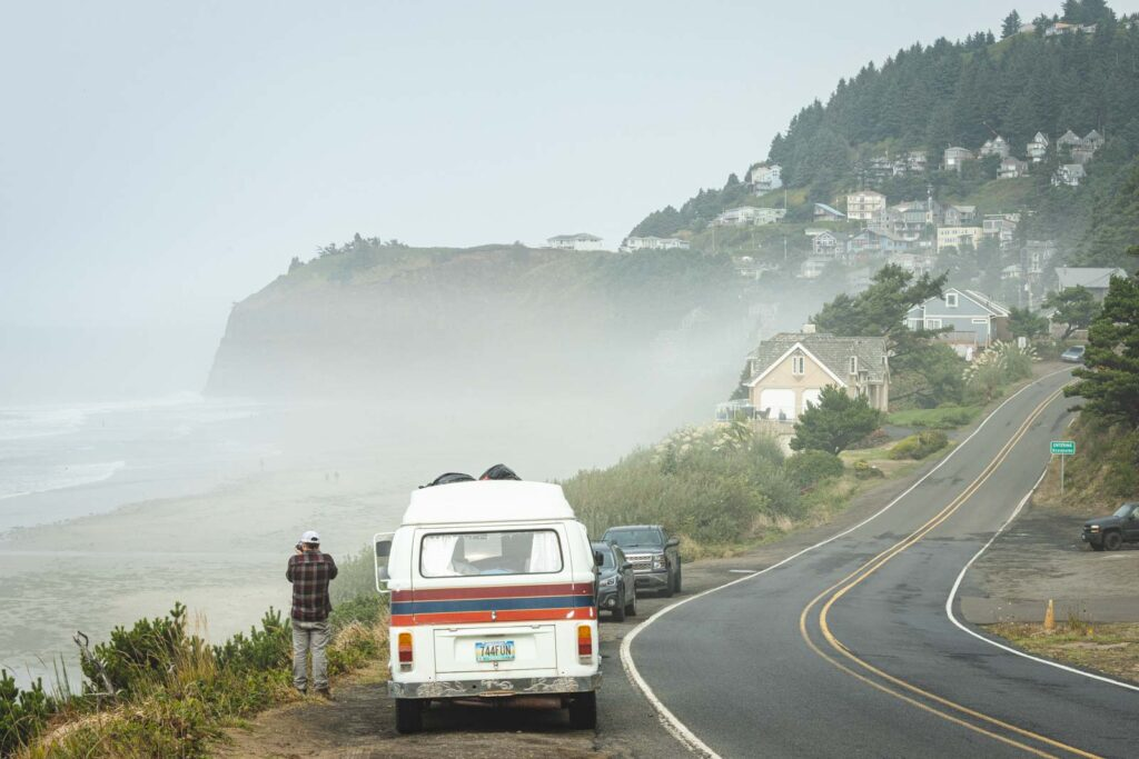 VW van with person behind it parked on the side of the road with foggy views of the beach and cape meares