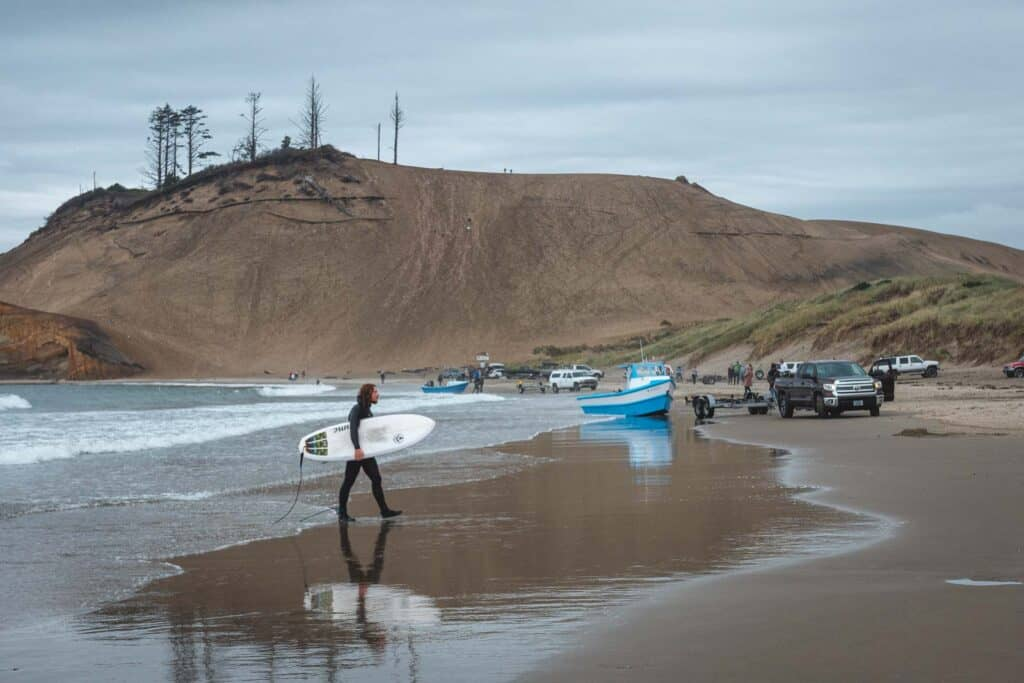 Surfer with surfboard walking out of the ocean with giant sand dune in background at Cape Kiwanda
