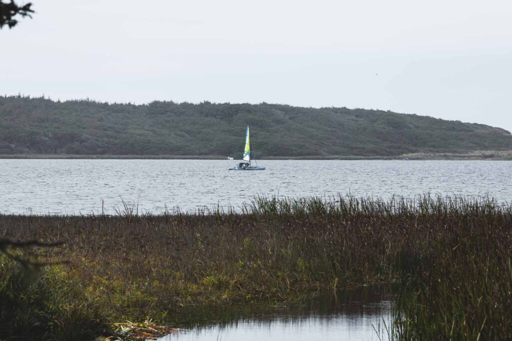Sailboat on water with forested hills in background at Flores Lake near Bandon Beach