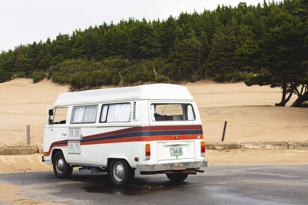 VW van parked in carpark with trees and sand in background at Sand Lake near Pacific City