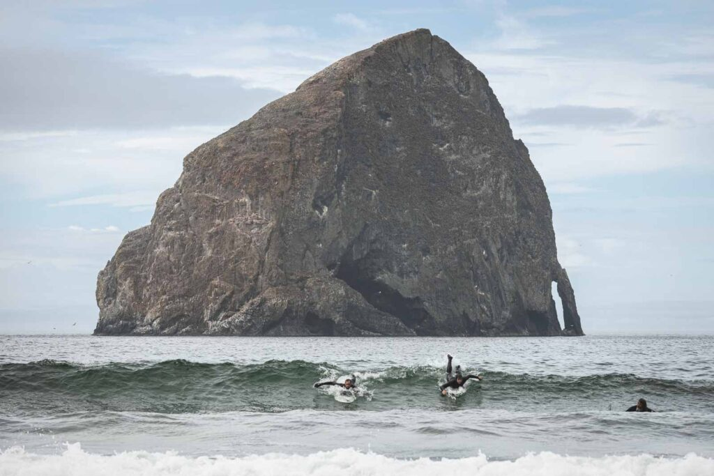 Two surfers surfing wave in ocean in front of large rock island in Pacific City, Oregon