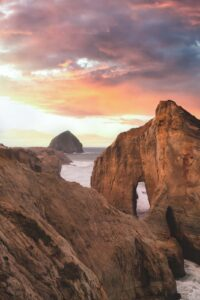 View over sea arch, coastline and island at sea at sunset from Cape Kiwanda