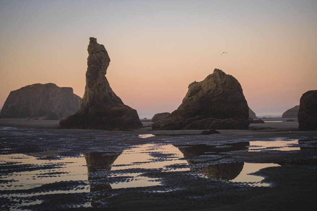 Wizards Hat rock formation on Bandon Beach, with reflections in water at sunset