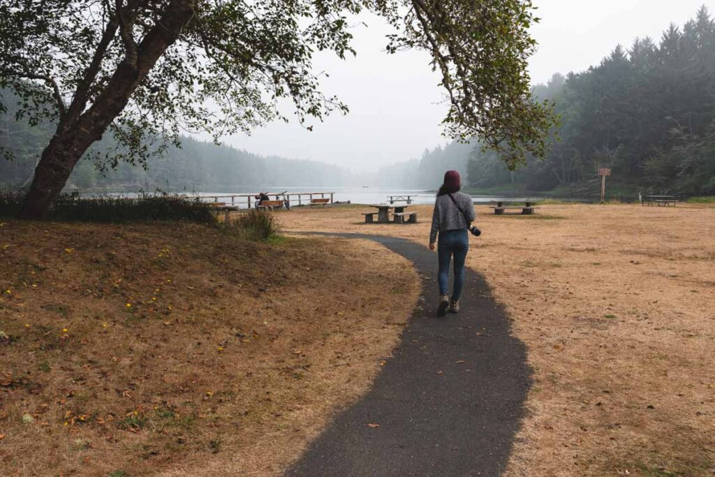 Woman walking on paved trail at Coffenbury Lake near Fort Stevens State Park