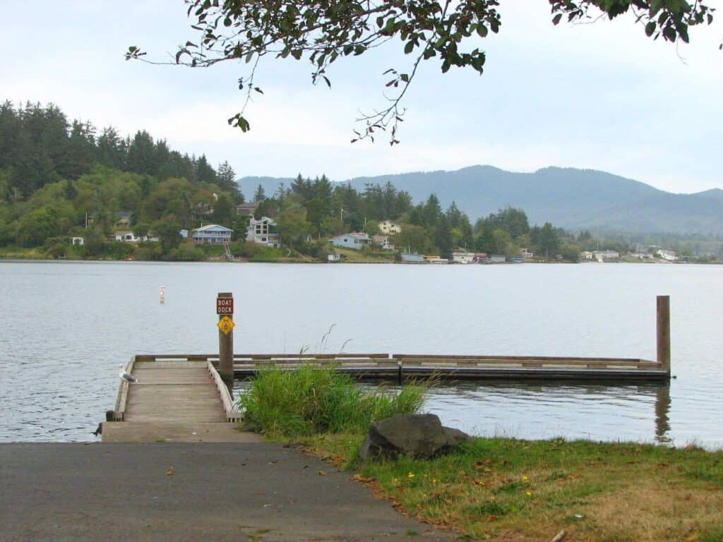 Dock on Devils Lake with trees and houses on peninsula in background near Lincoln City
