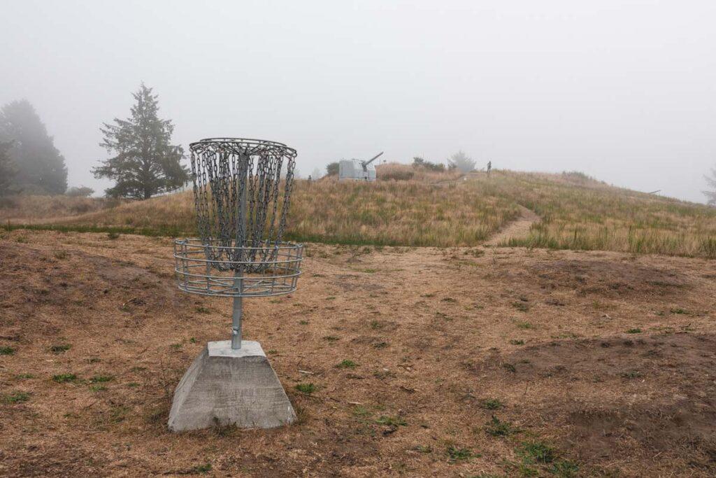 Disk golf basket on scrubby hill in Fort Stevens State Park