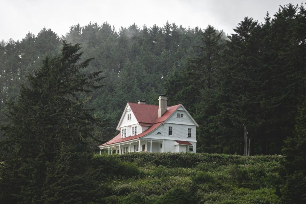 White house with red roof on a hill with forest in background at Heceta Head