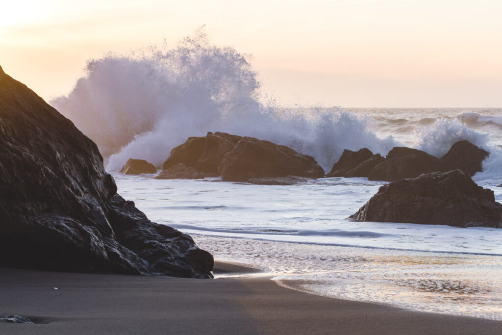 Nesika Beach at sunset with waves crashing against rocks by the shore