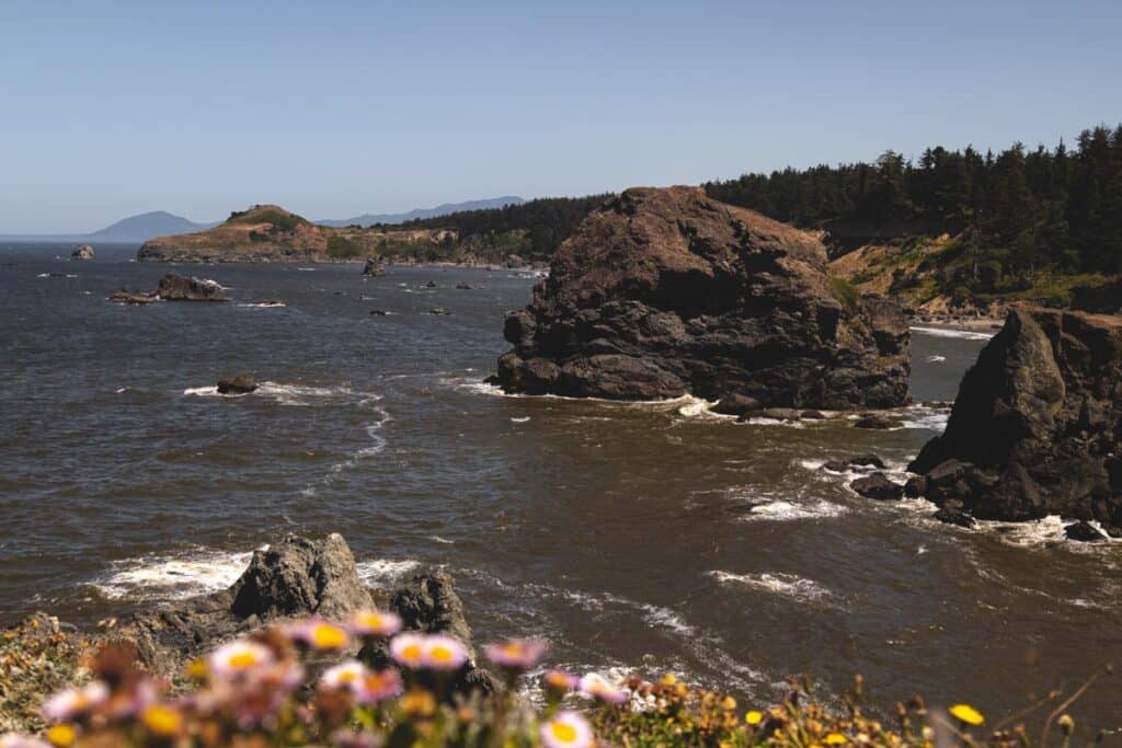 Aerial view over coastline with large rocks jutting out of ocean at Otter Point near Gold Beach Oregon