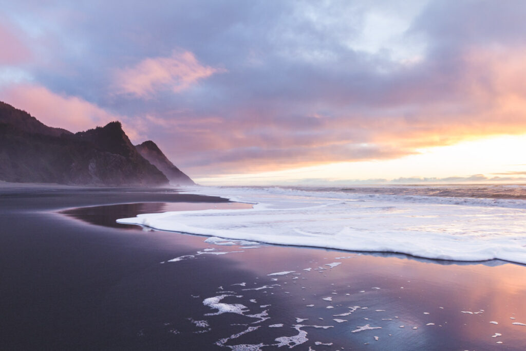 Gorgeous sunset scene in the Oregon coast with colorful clouds reflecting on the wet sand and waves and the hills of Cape Sebastian in the southern Oregon coast
