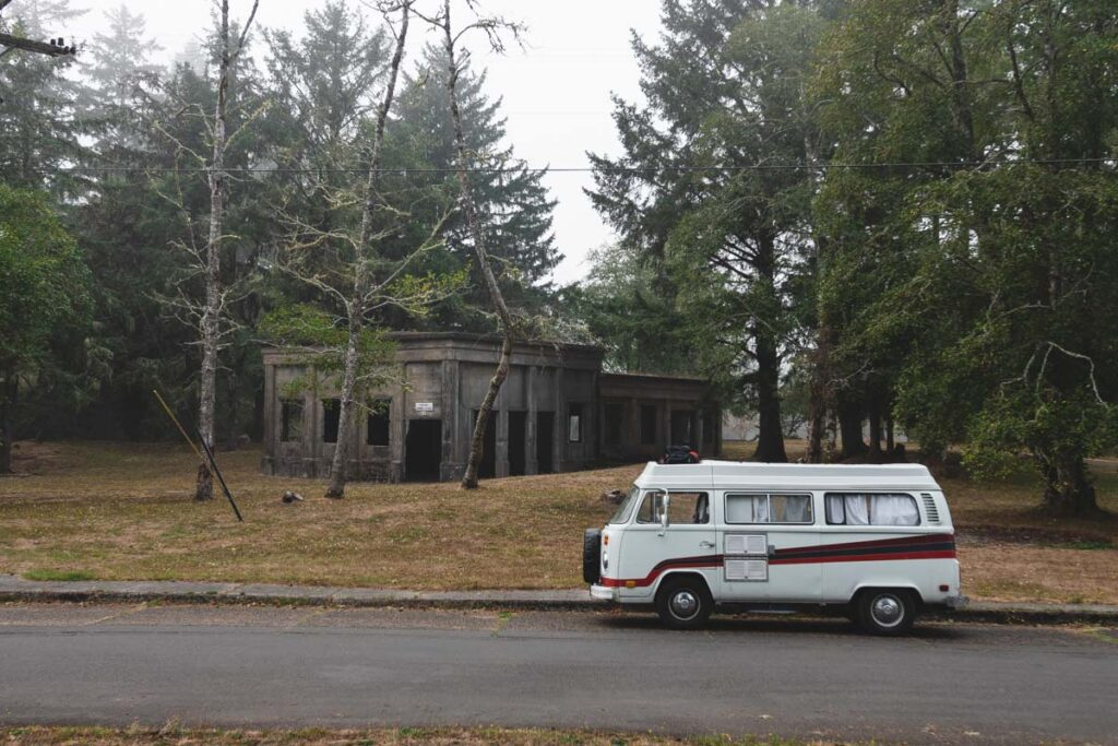 VW bus parked in front of ruins in the trees at Fort Stevens State Park
