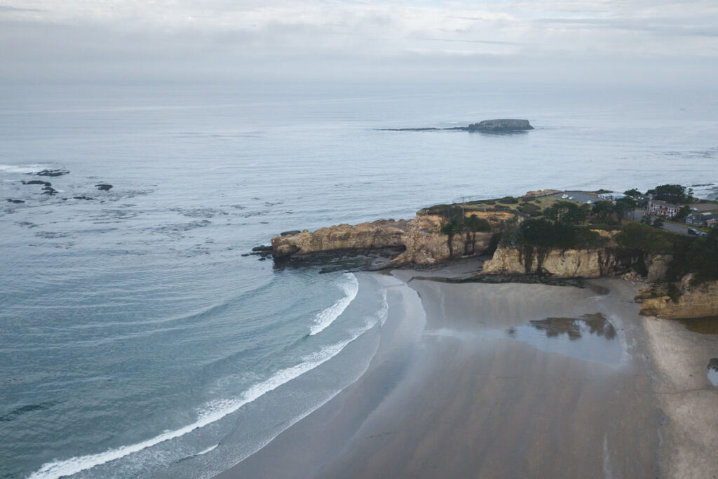Aerial view over beach, rocky headland and ocean at Otter Rock - an Oregon surf spot