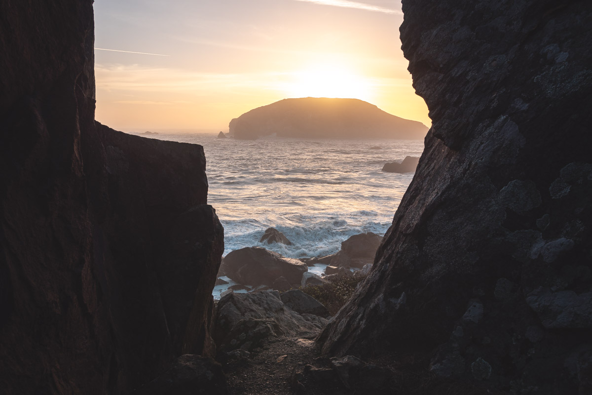 View of the sunset over the sea between rocks in harris state beach park