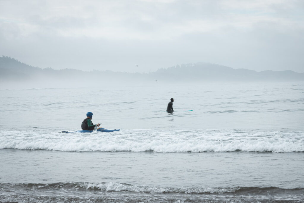 Two surfers in the ocean at Devils Punch Bowl beach in Oregon