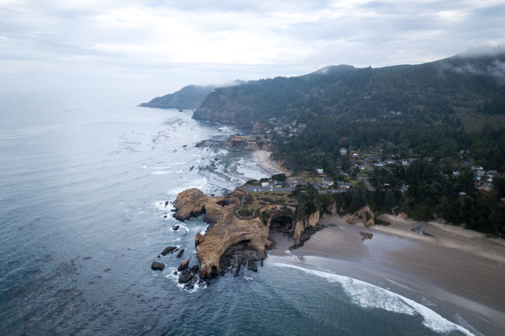 Aerial view over rocky outcrop and Devils Punch Bowl with beach on each side and forest behind it