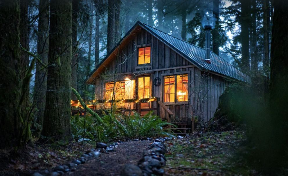 Cedarwood Cabin in the forest at night - one of the best cabins in Oregon
