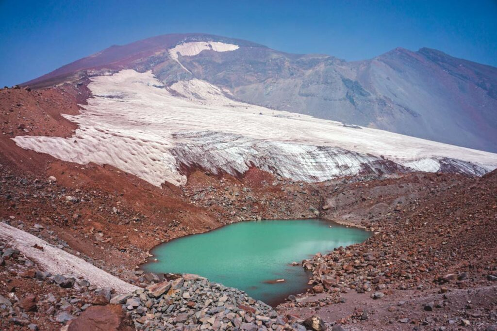 Turquoise lake surrounded by mountains with snow while hiking south sister