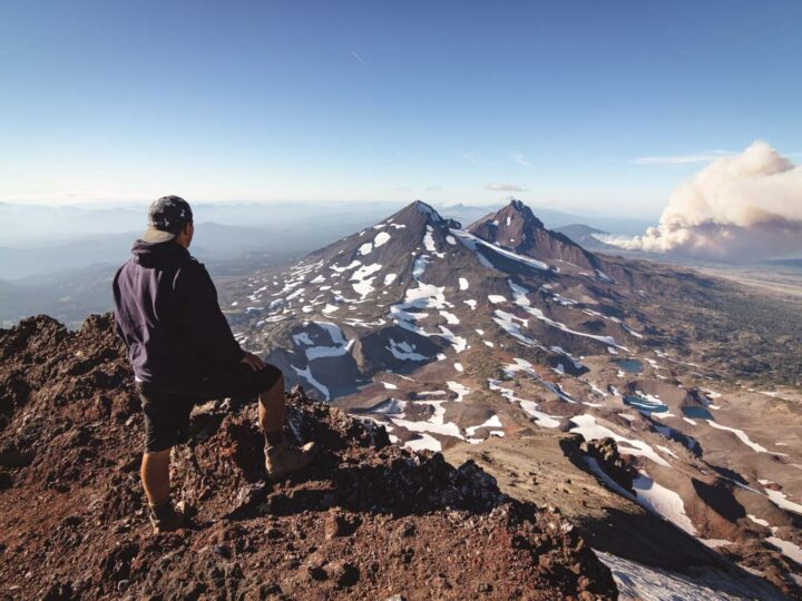 Hiker admiring the view from the summit of South Sister, Oregon