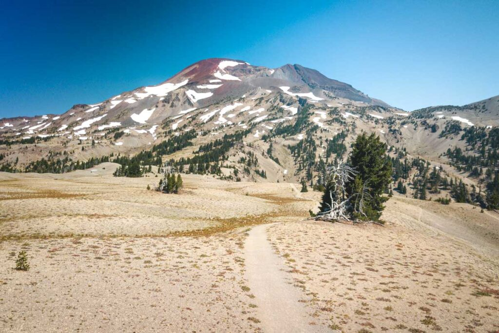 A sandy plateau with view of mountains while hiking south sister
