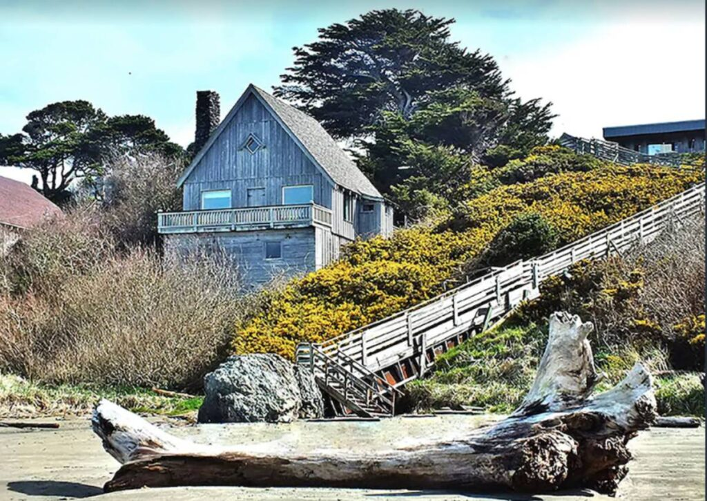 Old rustic beach cabin in oregon overlooking the beach with a large driftwood log in foreground